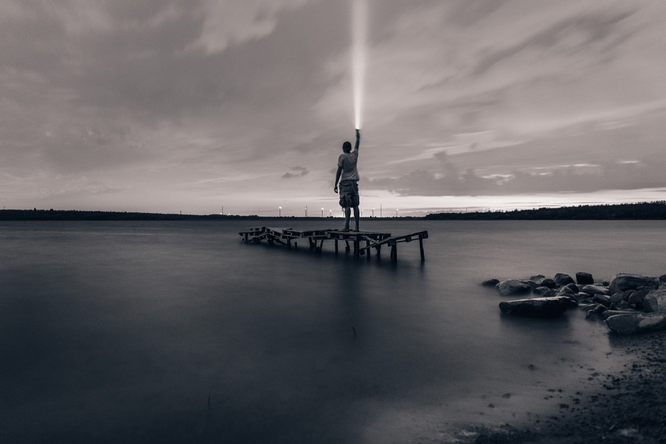 Man pointing flashlight to the sky - via Pixabay - no attribution required